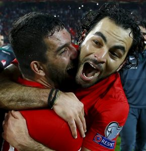 Selcuk Inan celebrates with captain Arda Turan after scoring the late free kick that secured Turkey's qualification to Euro 2016.