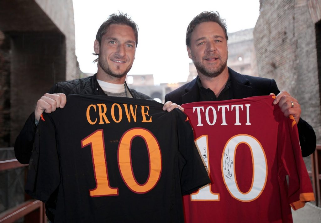 Two Gladiators, Francesco Totti & Russell Crowe, swap shirts at the Colosseum