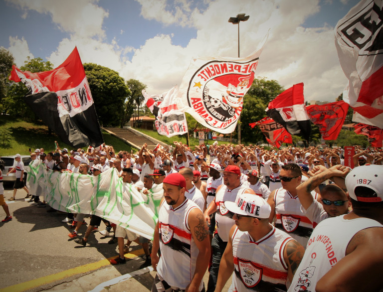 São Paulo FC's Torcida Independente arrive in the plaza holding a banner that reads '#ForçaChape'